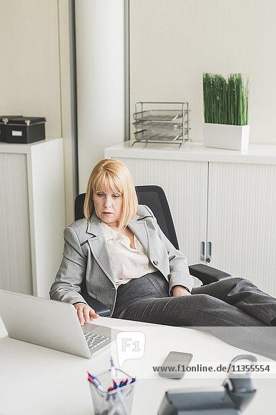 Reife Geschäftsfrau mit Füßen auf dem Schreibtisch mit Laptop