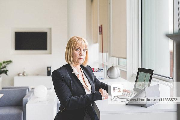 Portrait einer reifen Geschäftsfrau mit digitalem Tablett und Laptop am Büroarbeitsplatz
