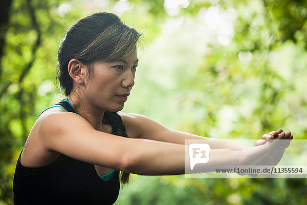 Mid adult woman exercising in forest  stretching