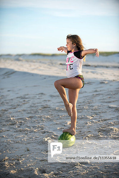 Young girl on beach  balancing on water melon