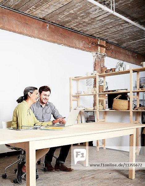 Kollegen am Schreibtisch im Workshop schauen auf Laptop-Computer
