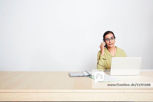Frau am Schreibtisch mit Telefon und Laptop