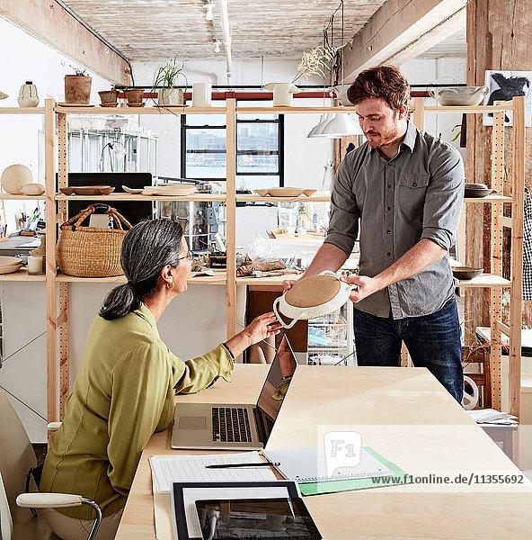 Mann zeigt Kollegen Keramikproben