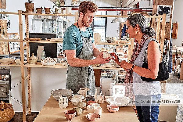 Töpfer in der Werkstatt zeigt Kundenkeramik