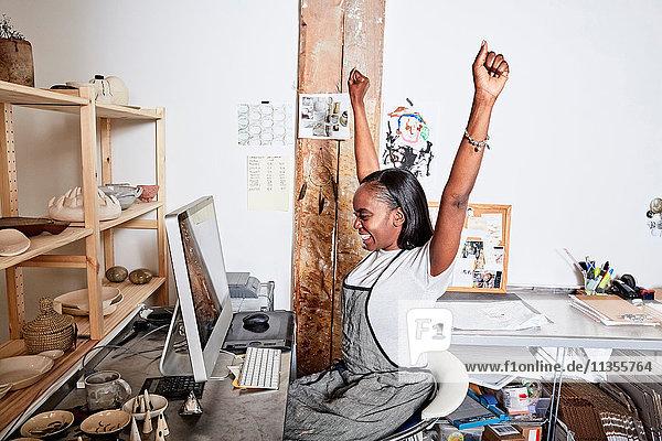 Frau am Schreibtisch mit Schürze Arme lächelnd erhoben