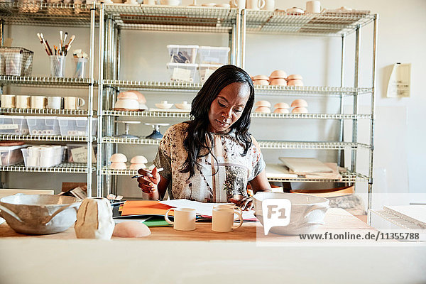 Woman in pottery workshop doing paperwork