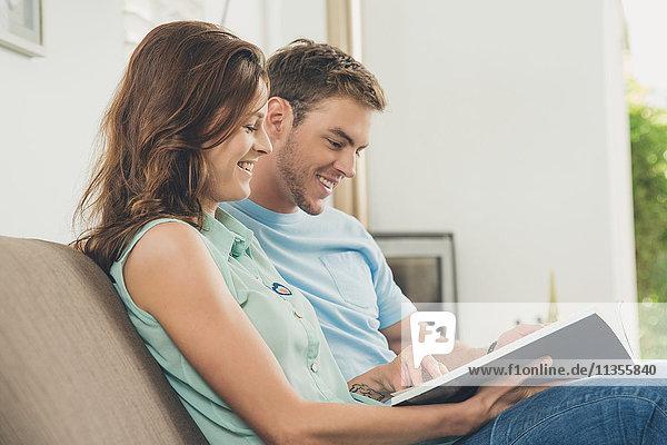 Ein Paar auf dem Sofa schaut lächelnd auf ein Buch
