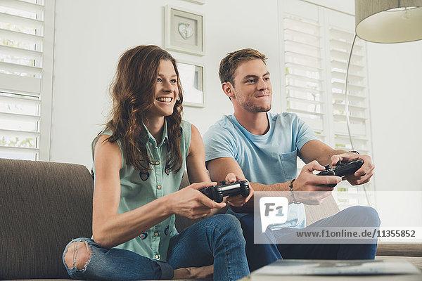 Paar auf dem Sofa mit Videospiel-Controller lächelnd