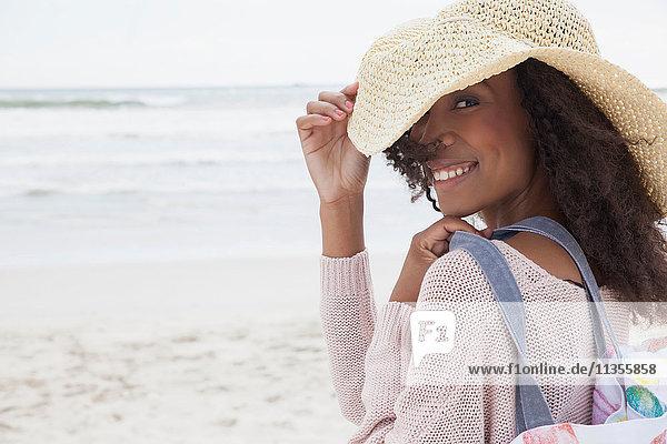 Junge Frau mit Hut am Strand