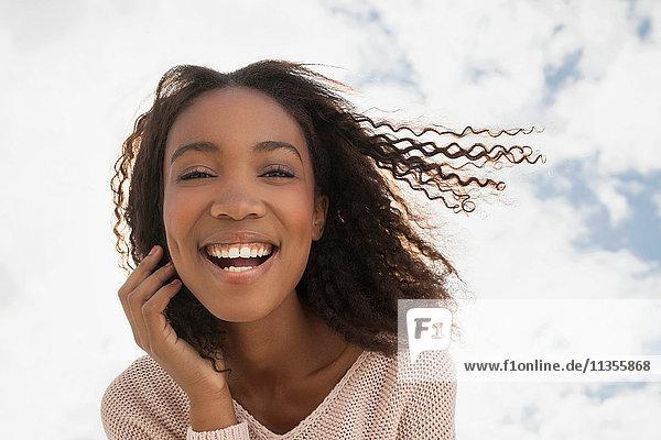 Glückliche junge Frau an einem windigen Tag