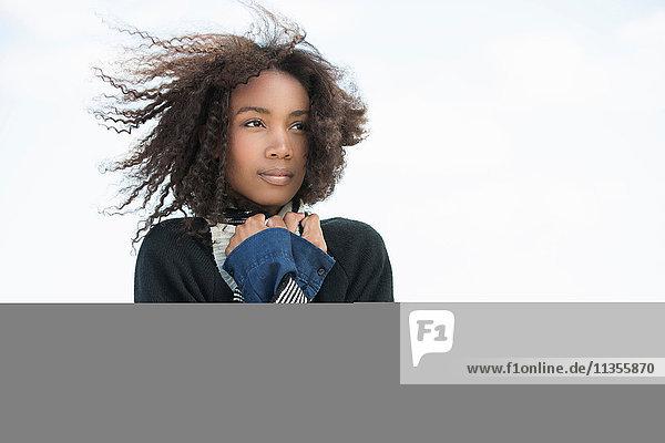 Junge Frau friert im Wind