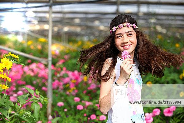 Glückliches Mädchen im Gewächshaus mit rosa Blumen