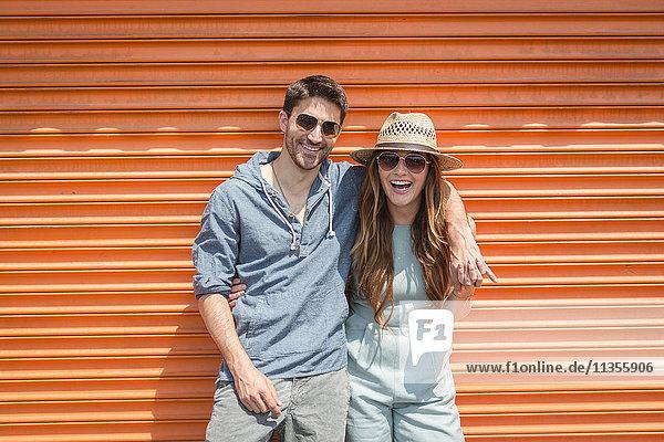 An orangefarbene Fensterläden gelehntes  in die Kamera blickendes Ehepaar  Coney Island  Brooklyn  New York  USA