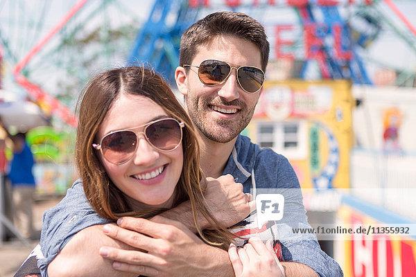 Paar mit Sonnenbrille schaut lächelnd in die Kamera  Coney Island  Brooklyn  New York  USA