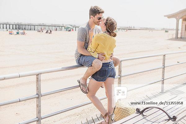 Paar auf dem Geländer beim Strandkuss  Coney Island  Brooklyn  New York  USA