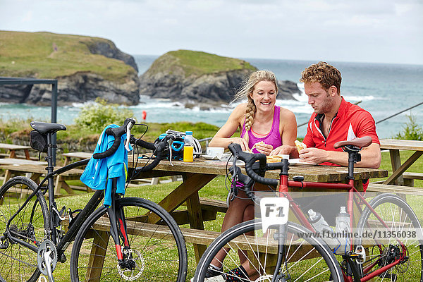 Cyclists relaxing at picnic table on hill overlooking ocean