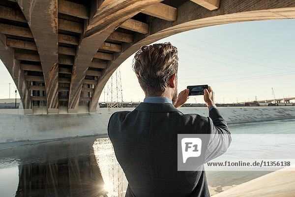 Businessman taking photograph using smartphone  Los Angeles river  California  USA