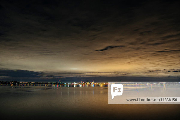 Distant view of city lights over Puget Sound at night  Seattle  Washington  USA