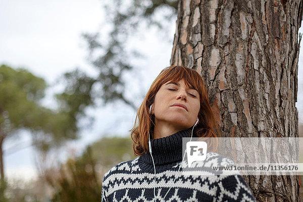An einen Baum gelehnte Frau mit Kopfhörern im Ohr  Augen geschlossen