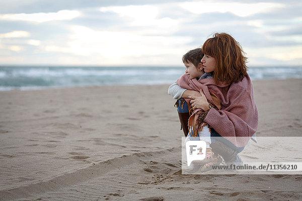 Mutter und Tochter in eine Decke gehüllt umarmen sich am Strand