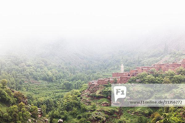 Nebliger Landschaftsblick auf das Dorf am Hang  Ourika-Tal  Marrakesch  Marokko