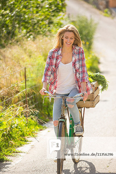 Frau fährt Fahrrad auf Landstraße lächelnd