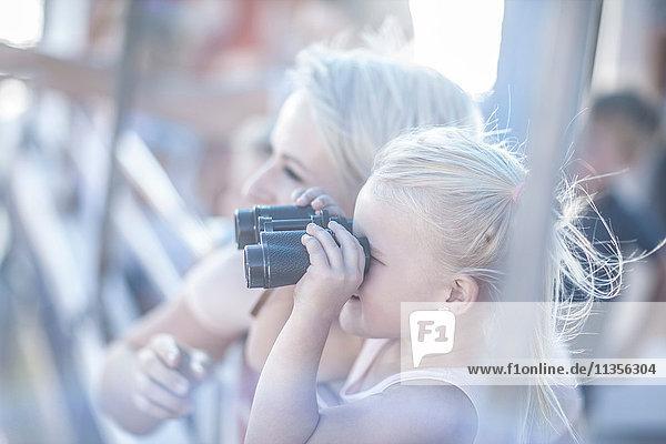 Süßes Mädchen schaut durch ein Fernglas auf einer touristischen Bootsfahrt  Kapstadt  Südafrika