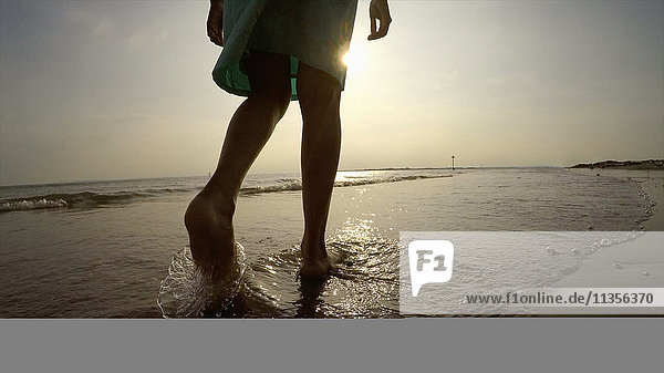 Legs of woman on coastline walking in ocean