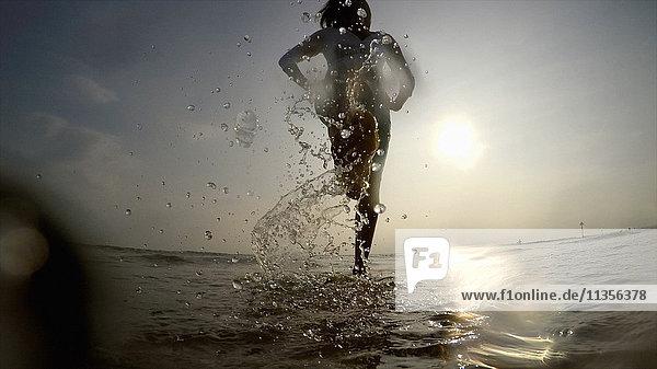 Woman in ocean splashing water
