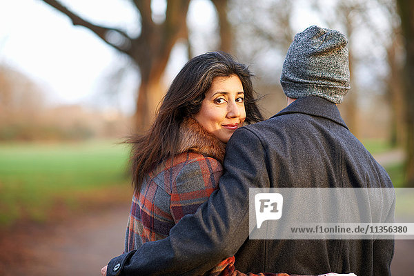 Mature couple with arms around each other looking over shoulder at camera smiling