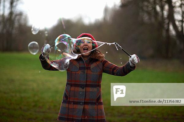 Frau im Park benutzt den Blasenzauberstab zum Blasenmachen