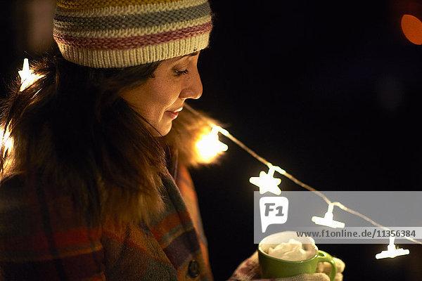 Frau hält Becher mit heißer Schokolade