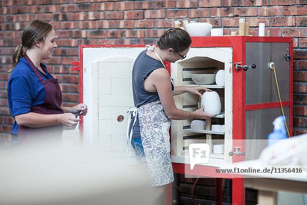 Female potter putting vase into workshop kiln