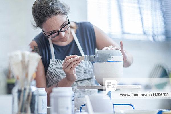 Töpferin bemalt Keramikglasur auf Vase in Werkstatt Töpferin bemalt Keramikglasur auf Vase in Werkstatt