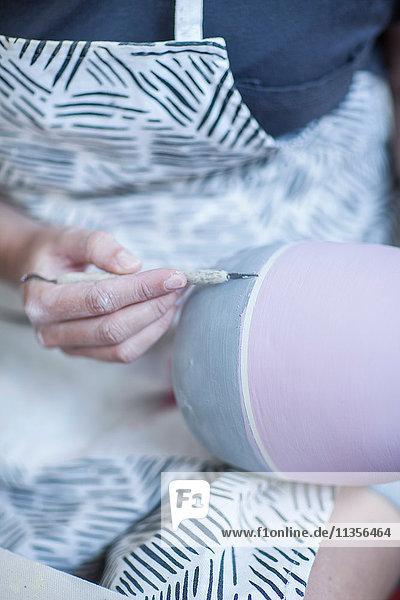 Nahaufnahme der Hände einer Töpferin  die in der Werkstatt Glasur auf eine Vase malt