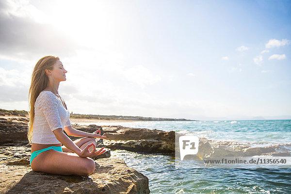 Junge Frau sitzt auf Felsen am Meer  in Yogastellung
