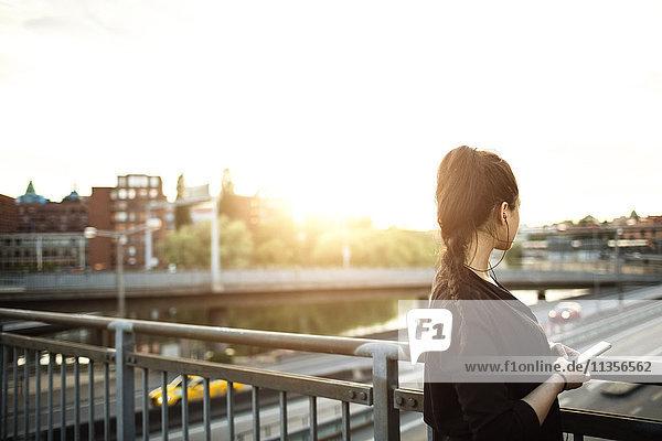 Seitenansicht der Frau mit auf der Brücke stehendem Handy gegen den Himmel