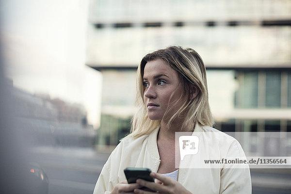 Junge Frau mit Handy gegen Bauen in der Stadt