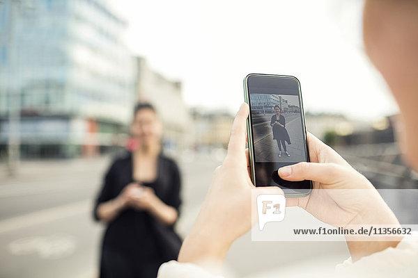 Abgeschnittenes Bild einer Frau  die einen Freund in der Stadt fotografiert.
