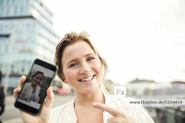 Porträt der glücklichen Frau mit Foto im Handy