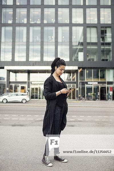 Frau mit Handy gegen Bauen in der Stadt