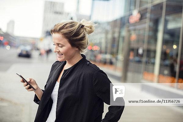 Glückliche Frau mit Handy im Stehen in der Stadt