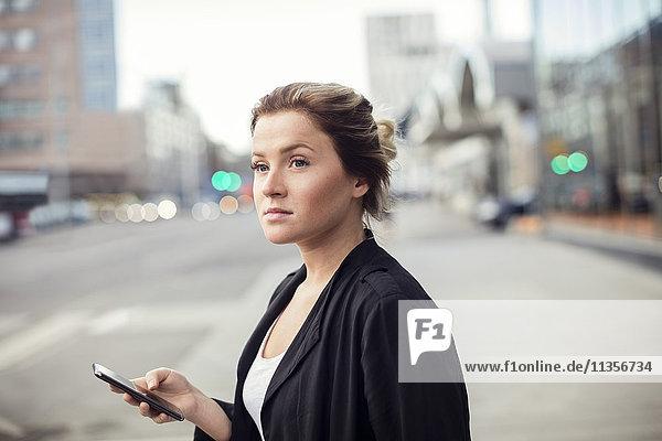 Frau mit Handy im Stehen in der Stadt