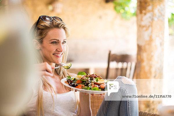 Junge Frau entspannt sich auf der Gartenterrasse und isst Salat