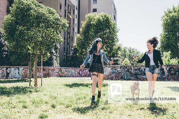 Zwei junge Frauen mit Pitbull-Terrier im Stadtpark