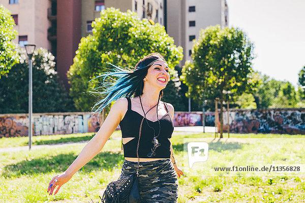 Junge Frau lachend und rennend im Stadtpark