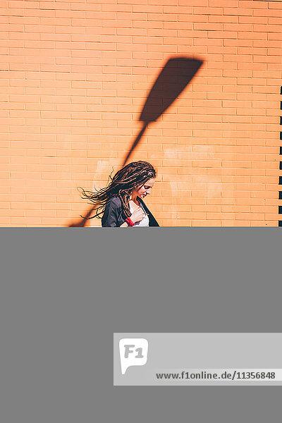 Junge Frau mit Dreadlocks betrachtet Pitbull-Terrier vor orangefarbener Wand