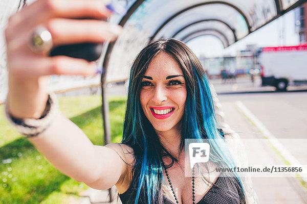 Junge Frau mit tauchgefärbten blauen Haaren nimmt Smartphone im städtischen Buswartehäuschen