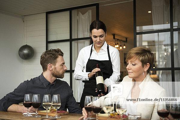 Frau in Schürze mit Weinflasche für Geschäftsleute am Tisch