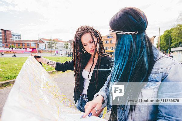 Zwei junge Frauen mit Dreadlocks und gefärbten Haaren  die auf die Karte im Stadtpark zeigen.